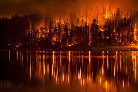 A fire approaches the shore of Bass Lake in California