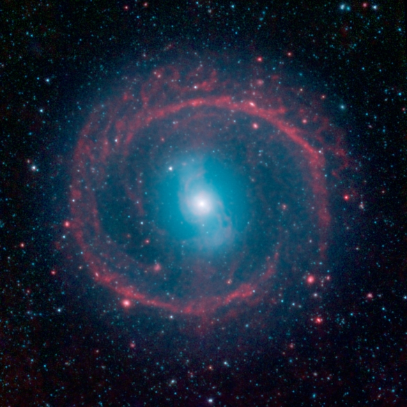 "It might look like as spoked wheel or even a ""Chakram"" circular weapon wielded by television's fictional warrior Xena, but this ringed galaxy is actually a vast place of stellar life. A newly released image from NASA's Spitzer Space Telescope shows the ga"